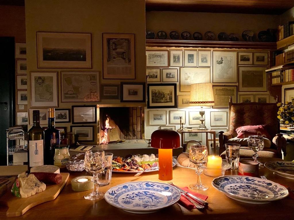 Altes Geschirr und moderne Lampe vor Kamin: Flackerndes Feuer sorgt für eine gemütliche Atmosphäre.