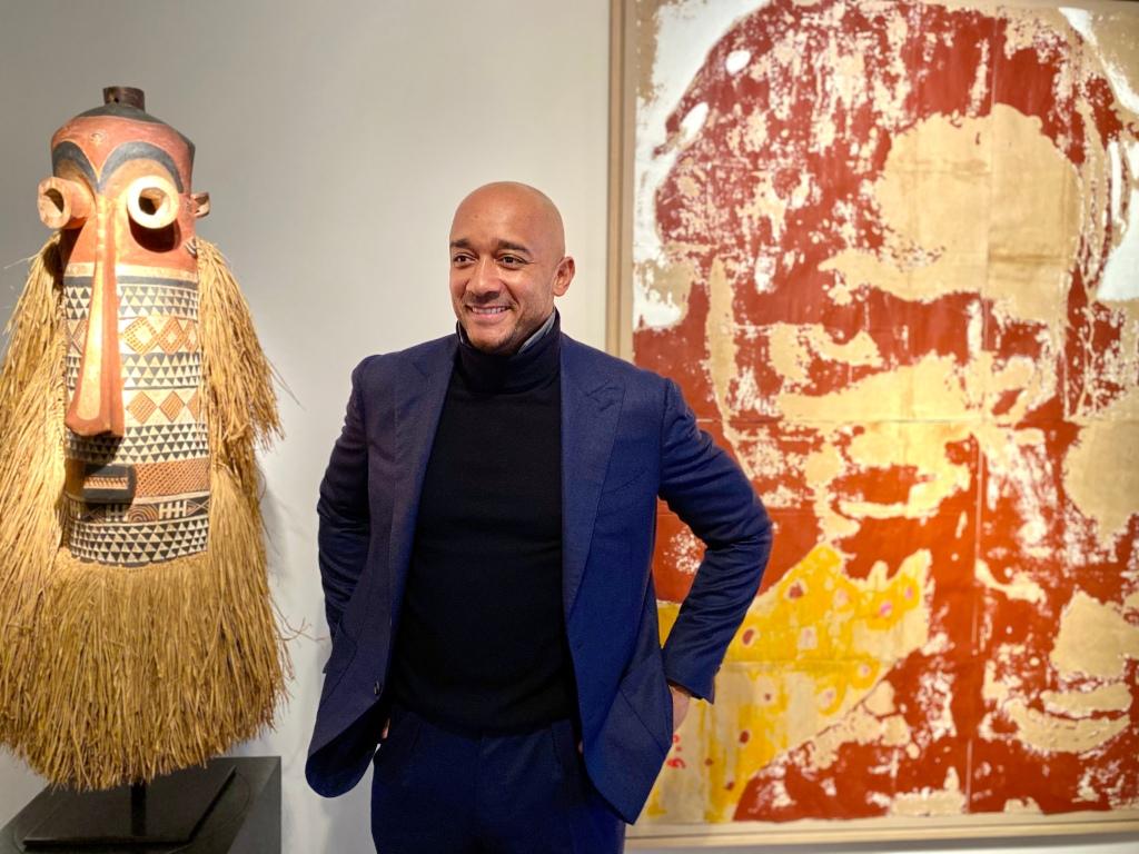 Der Galeriegründer Didier Claes zwischen einer Maske der Pende aus dem Kongo und dem unbetitelten Gemälde von Armand Boua.