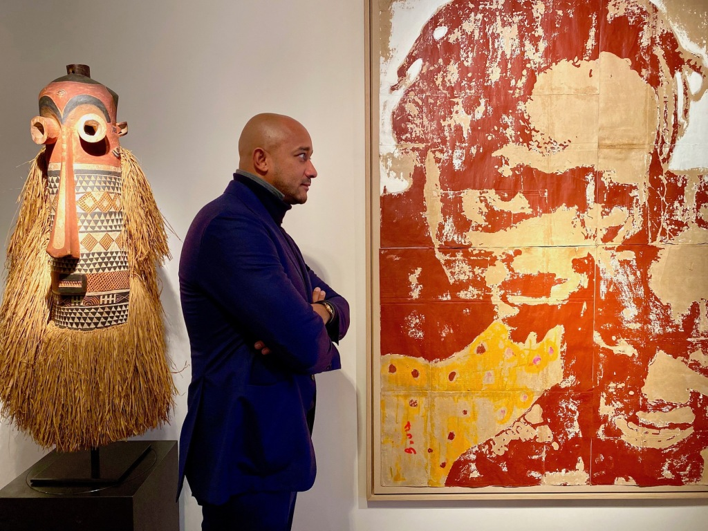 Gallery founder Didier Claes between a mask of the Pende from the Congo and an untitled painting by Armand Boua.